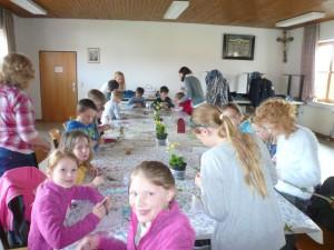 Die Kinder basteln an ihren Ketten bzw. Schlüsselanhängern. Die Schlüsselblumen stehen noch auf dem Tisch