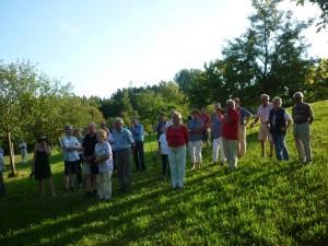 Gespannt beobachten alle Teilnehmer den Flug der Bienen vor dem Bienenhaus und lauschen, was Hans Schmid dazu erzählt.